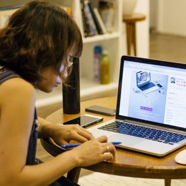 Woman working on a laptop at a desk.